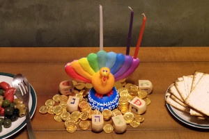 "A turkey-shaped Menorah, dubbed a ""Menurkey,"" is surrounded by gelt and dreidls at a 2013 Thanksgivukkah celebration. Creative commons image by Beowabbit"