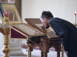 A member of the HOly Father of the First Ecumenical Council kisses an icon on the 7th Sunday of Pascha, or Easter. Creative commons image by the St. Petersburg Orthodox Theological Academy